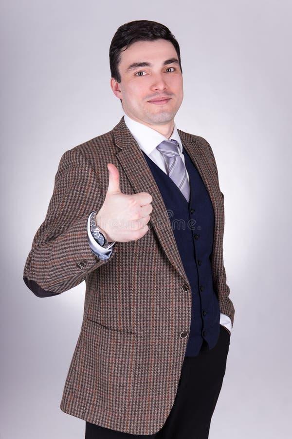 Le portrait du jeune homme heureux d'affaires manie maladroitement au-dessus du gris photographie stock