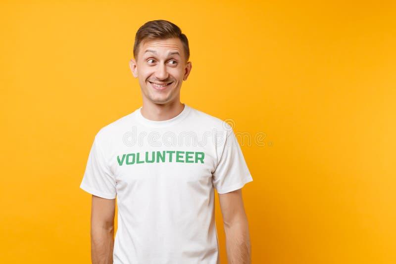 Le portrait du jeune homme satisfaisant de sourire heureux dans le T-shirt blanc avec le volontaire écrit de titre de vert d'insc image stock