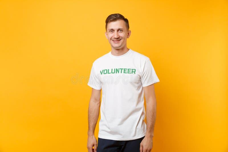Le portrait du jeune homme satisfaisant de sourire heureux dans le T-shirt blanc avec le volontaire écrit de titre de vert d'insc photographie stock