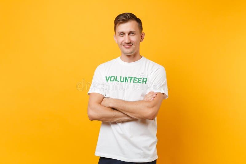 Le portrait du jeune homme satisfaisant de sourire heureux dans le T-shirt blanc avec le volontaire écrit de titre de vert d'insc images stock