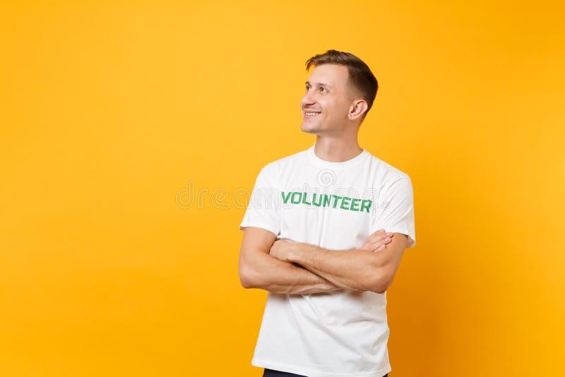 Le portrait du jeune homme satisfaisant de sourire heureux dans le T-shirt blanc avec le volontaire écrit de titre de vert d'insc images libres de droits