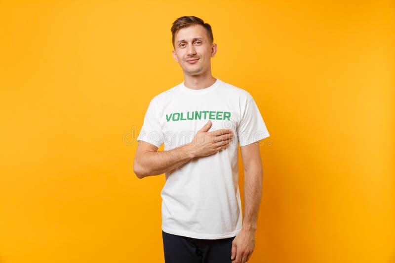Le portrait du jeune homme satisfaisant de sourire heureux dans le T-shirt blanc avec le volontaire écrit de titre de vert d'insc photos stock