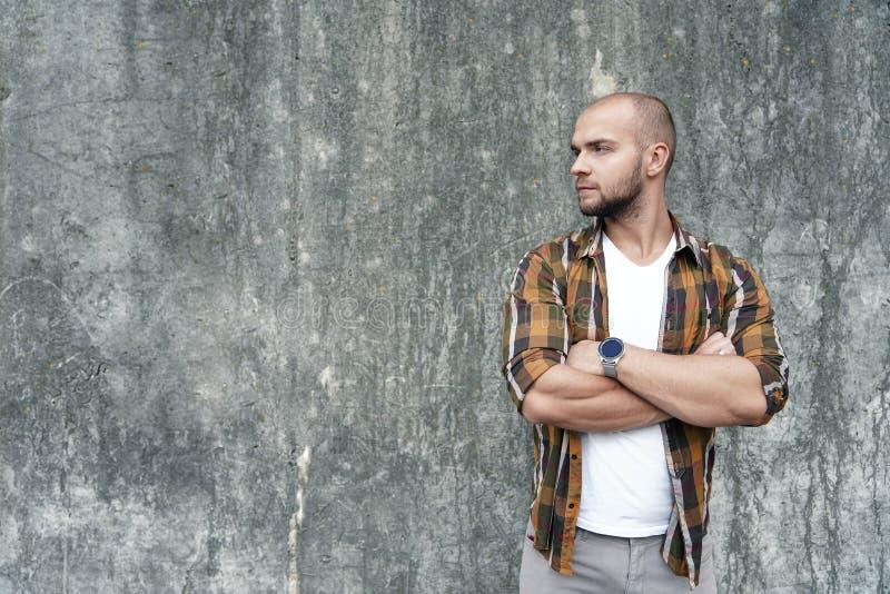 Le portrait du jeune type barbu audacieux beau se tenant dehors contre le mur gris de grenier regardant de côté avec ses mains a  image libre de droits