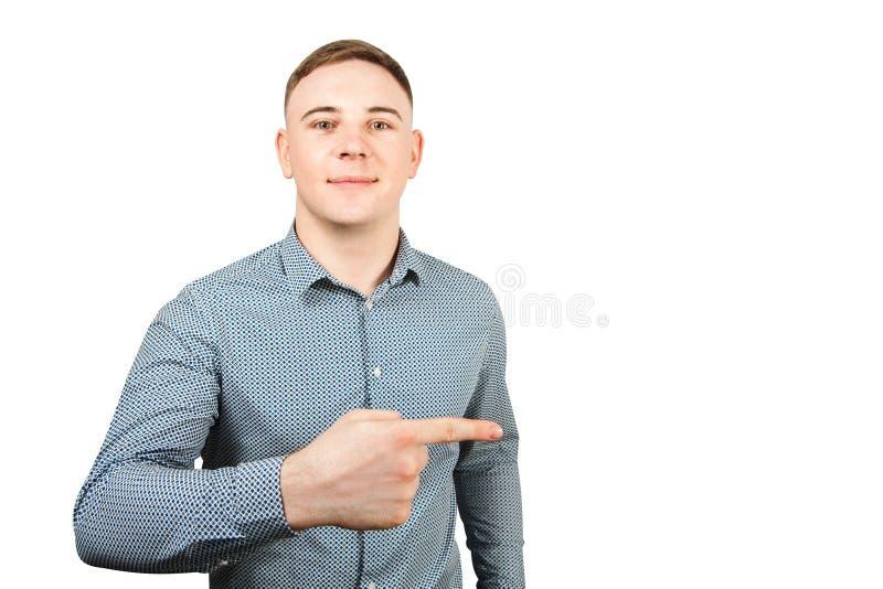 Le portrait du jeune type beau habillé dans la chemise bleue montre l'index et les sourires D'isolement sur le fond blanc photo libre de droits