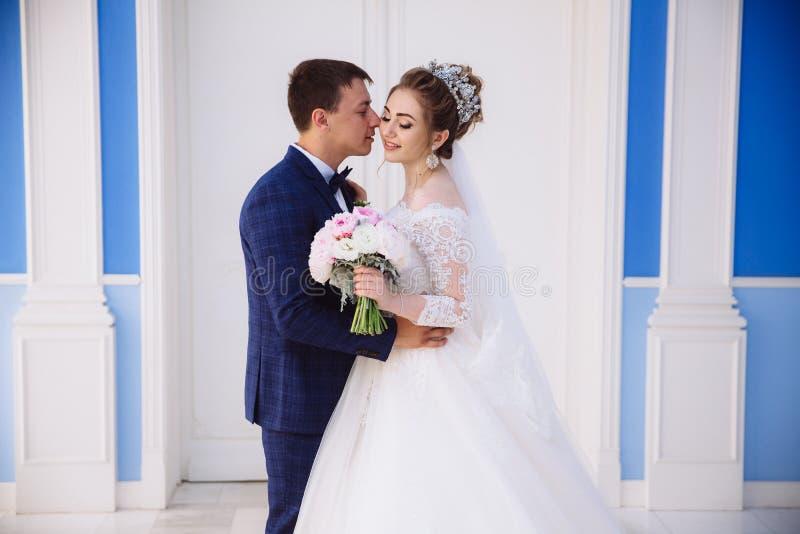 Le portrait du marié tient fermement sa jeune mariée par la taille et l'embrasse tendrement, la fille sourit et admire images stock