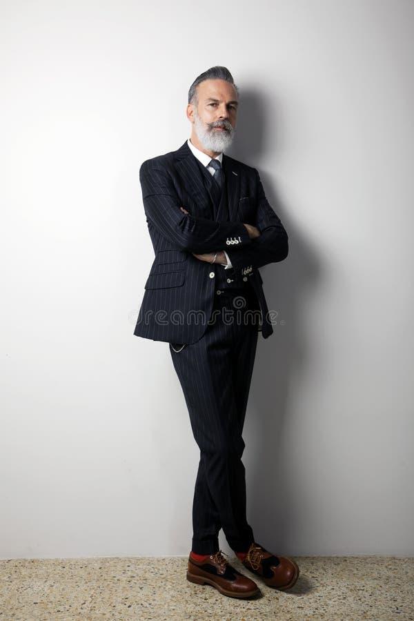 Le portrait du milieu barbu sûr a vieilli le monsieur portant le costume à la mode se tenant au-dessus du fond blanc vide studio images stock