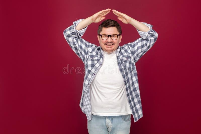 Le portrait du milieu beau heureux a vieilli l'homme dans la chemise occasionnelle et des lunettes à carreaux se tenant avec le g photographie stock