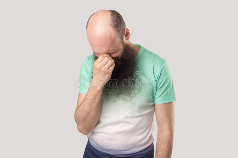 Le portrait du milieu déprimé triste seul a vieilli l'homme chauve avec la longue barbe dans la position vert clair de T-shirt ma images stock