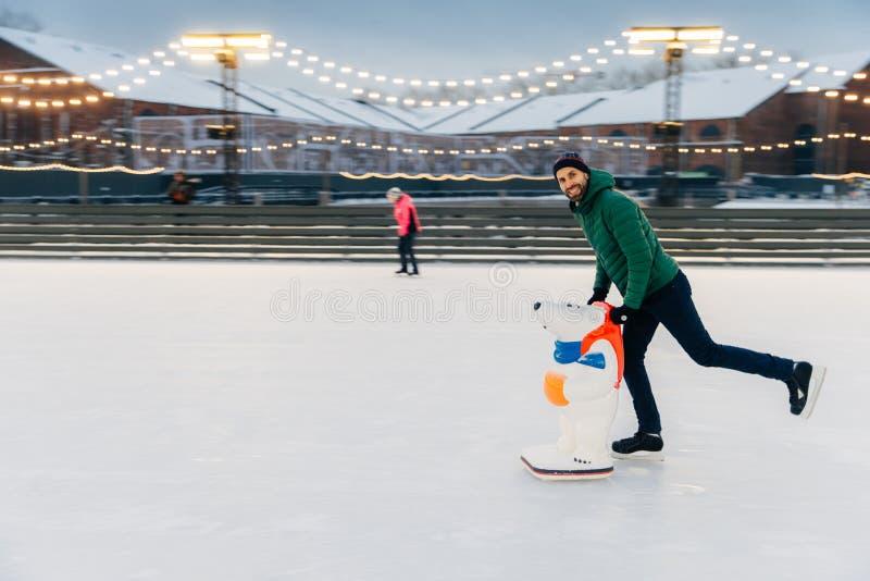 Le portrait du patineur masculin âgé par milieu heureux se tient sur l'anneau de glace, en photographie stock