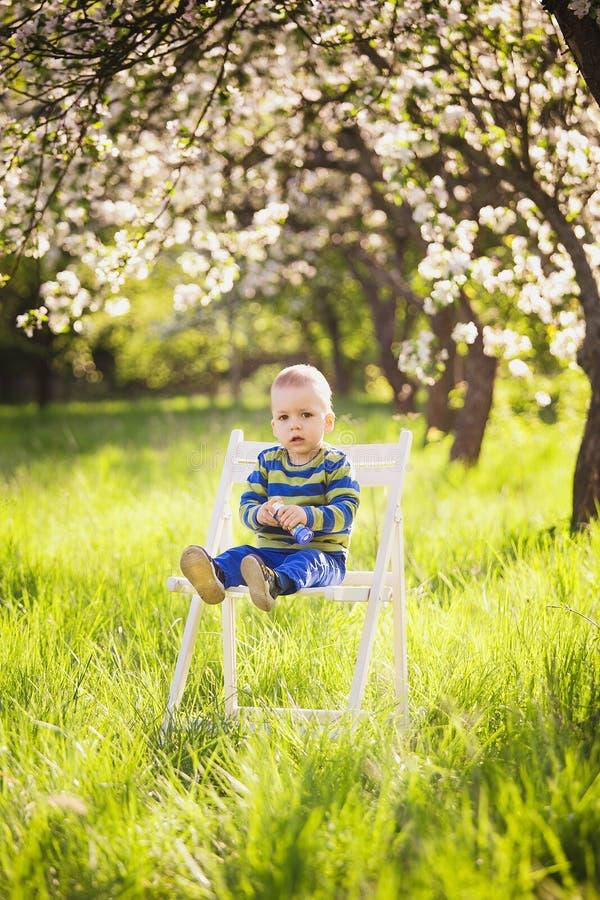 Le portrait du petit garçon mignon s'asseyant sur le blanc a peint Chai en bois image libre de droits