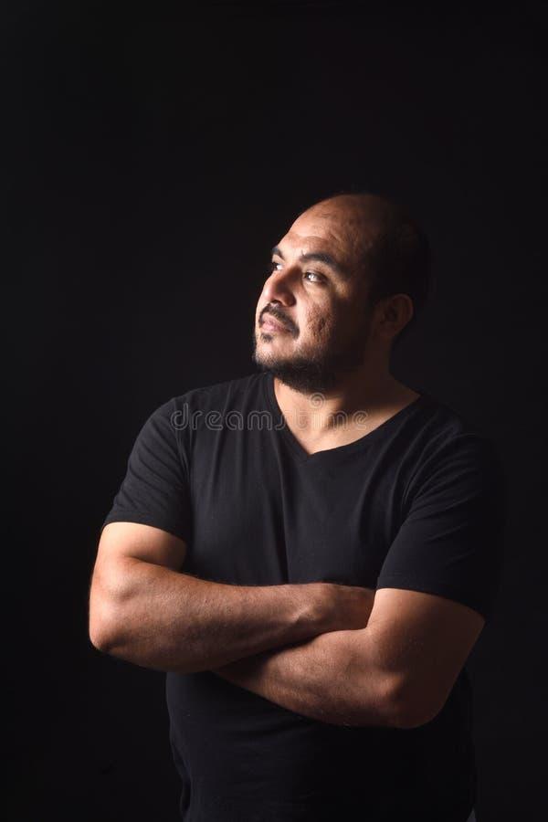 Le portrait du profil des bras latino-américains d'un homme a croisé sur le fond noir, sérieux photos stock