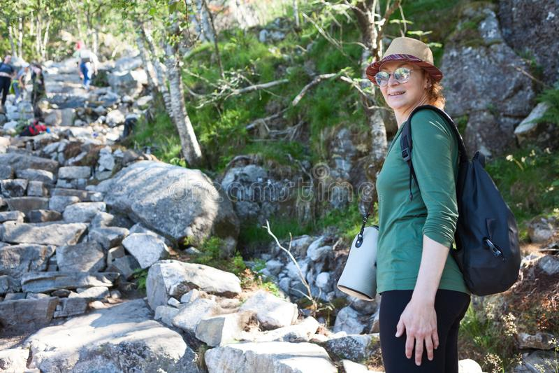 Le portrait du randonneur européen mûr de femme tenant la manière en pierre proche à la montagne, sac à dos est allumé arrière images stock