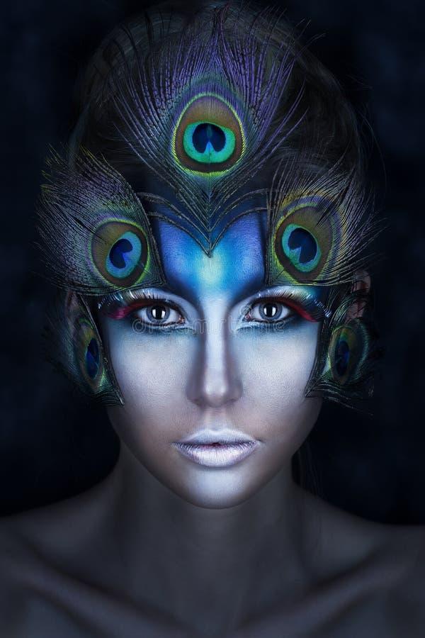 Le portrait du ` s de fille avec un maquillage d'avant-garde et des plumes d'un paon dans des tons bleus photo stock