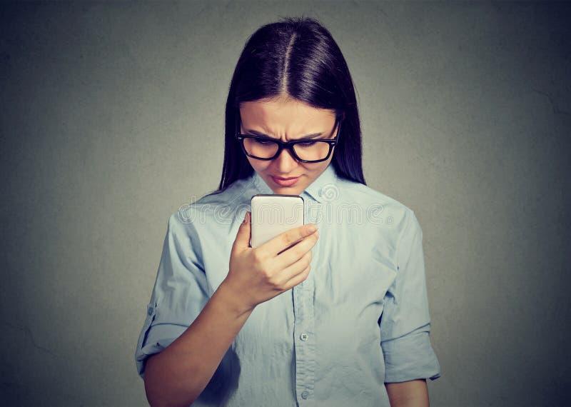 Le portrait du service de mini-messages parlant de femme sérieuse triste de renversement à un téléphone a contrarié avec la conve photographie stock libre de droits