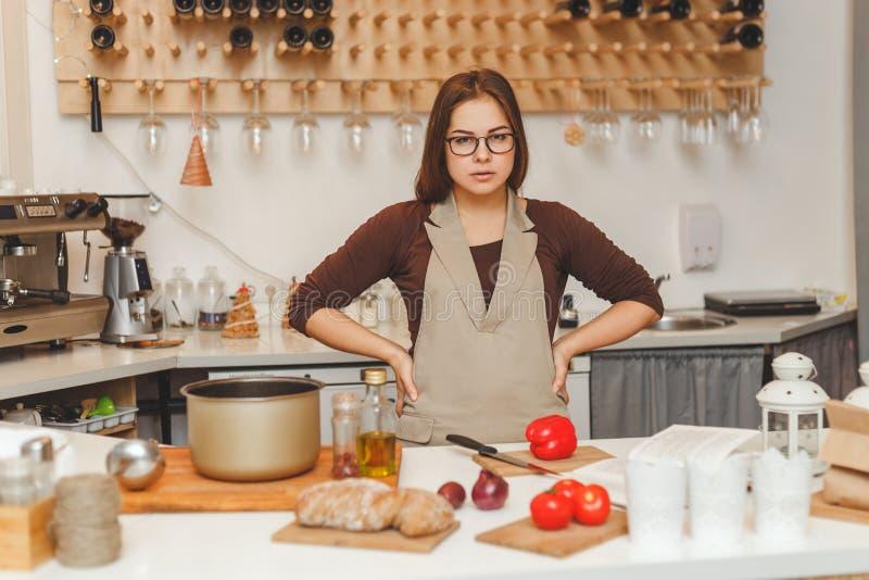 Le portrait du tablier de port de belle femme au foyer de ypung fait cuire la soupe au tomat o photo stock