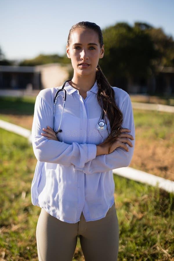 Le portrait du vétérinaire féminin avec des bras a croisé la position à la grange photo libre de droits