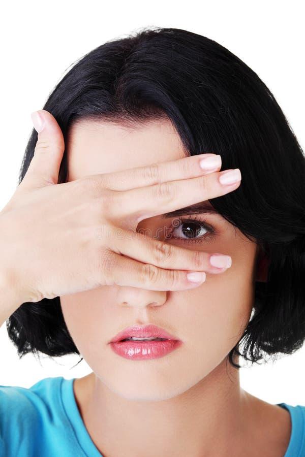 Le portrait du visage de la jeune femme attirante a couvert l'oeil à la main. images stock