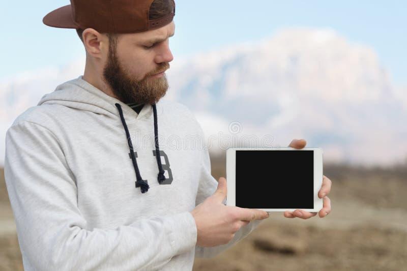 Le portrait en gros plan d'un hippie dans un chapeau brun tient en plein air un PC blanc de comprimé dans des ses mains Regards b photos libres de droits