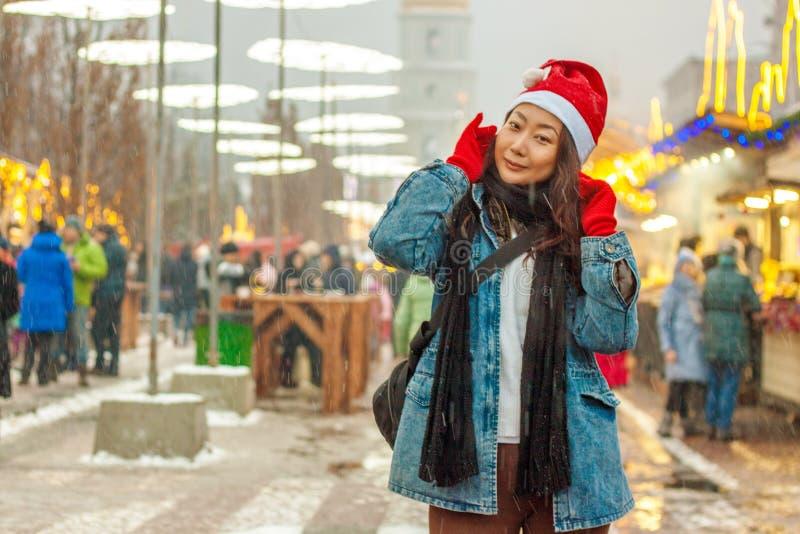 Le portrait en gros plan d'une belle fille asiatique heureuse dans un chapeau rouge de Santa Claus tenant un smartphone se tient  image libre de droits