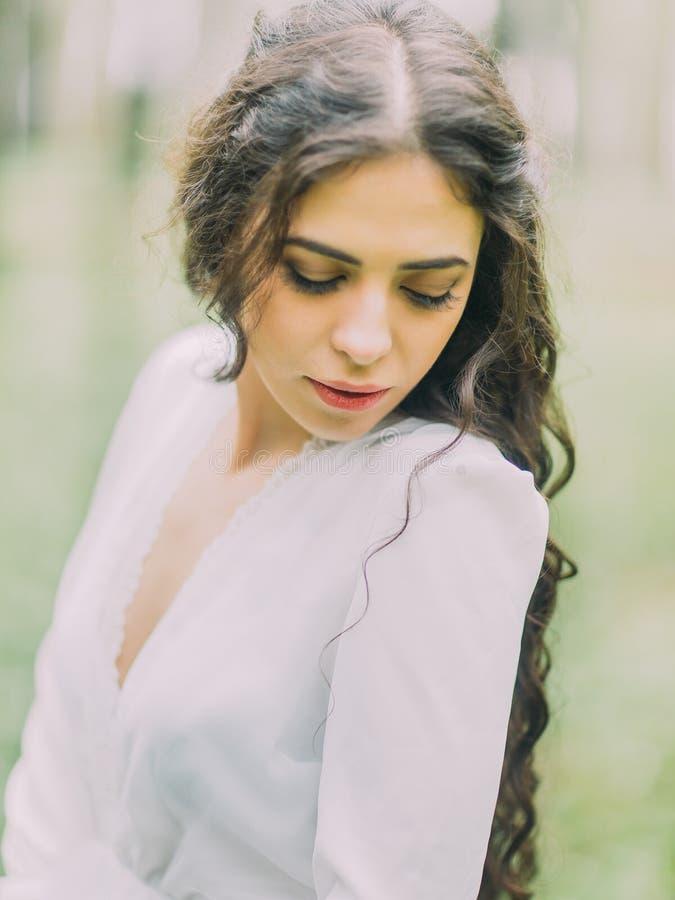 Le portrait en gros plan de la belle femme dans la robe de mariage blanche regardant la terre dans la forêt verte images stock