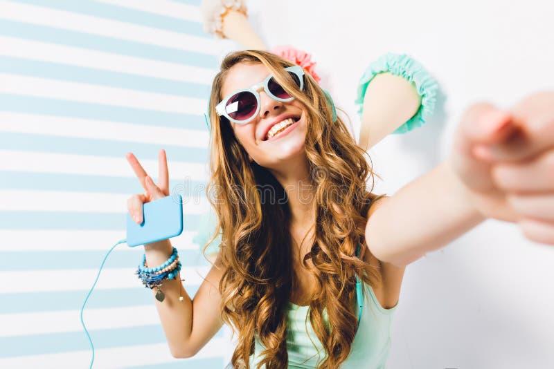 Le portrait en gros plan de la fille heureuse dans des lunettes de soleil et les bracelets à la mode posant avec la paix signent  photo libre de droits