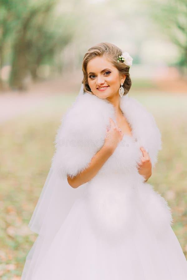 Le portrait en gros plan de la jeune mariée blonde heureuse dans le boa blanc de robe et de fourrure sur la ruelle à l'automne se images stock