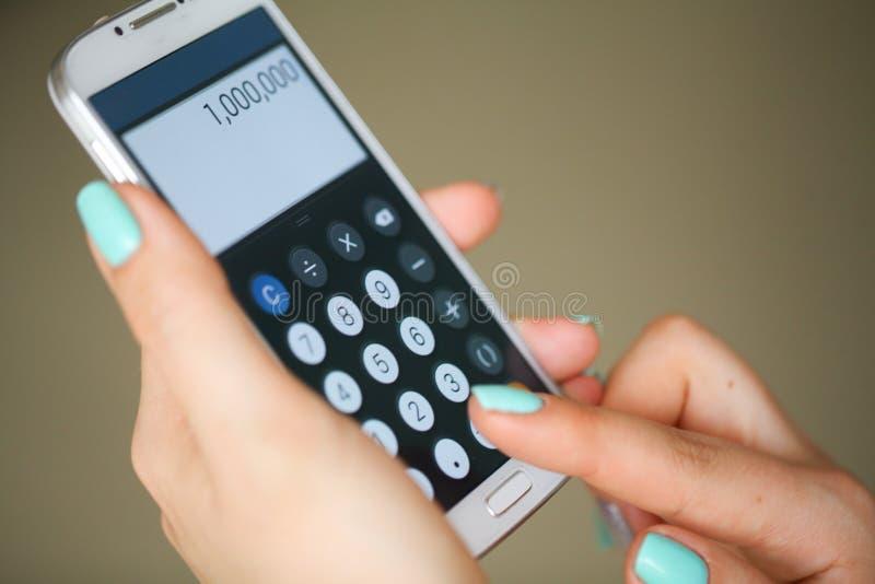 Le portrait en gros plan du bleu cloue la main de femme d'affaires tout en à l'aide de la calculatrice image stock