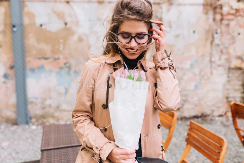 Le portrait en gros plan extérieur de la belle fille inhale le parfum de fleur une date dans un café Jeunes gênés de charme photo libre de droits