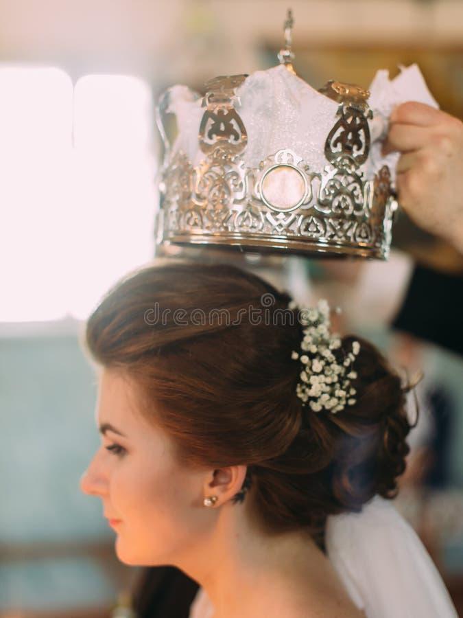 Le portrait en gros plan latéral de la jeune mariée pendant le couronnement de mariage images stock