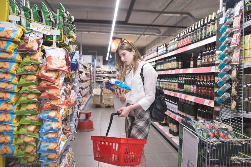 Le portrait est une fille élégante qui choisit des puces dans le supermakret L'acheteuse de fille achète à un supermarché image stock