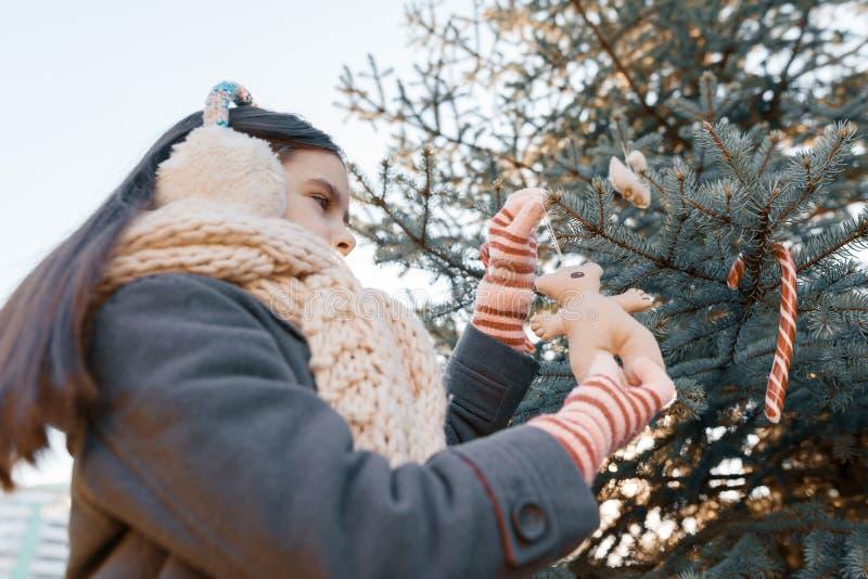 Le portrait extérieur d'hiver de la fille d'enfant près de l'arbre de Noël, fille de sourire décore l'arbre de Noël avec le jouet photographie stock libre de droits