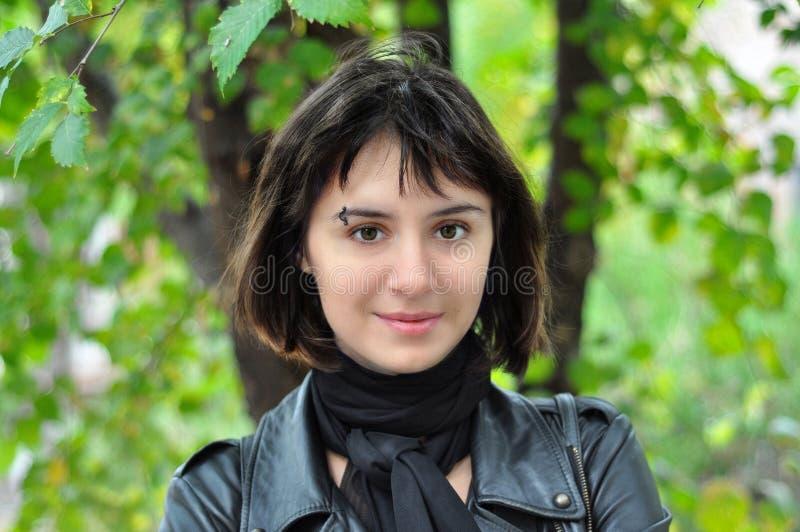 Le portrait extérieur d'une belle jeune fille s'est habillé dans une veste en cuir de style de roche sur le fond des verts juteux photos stock