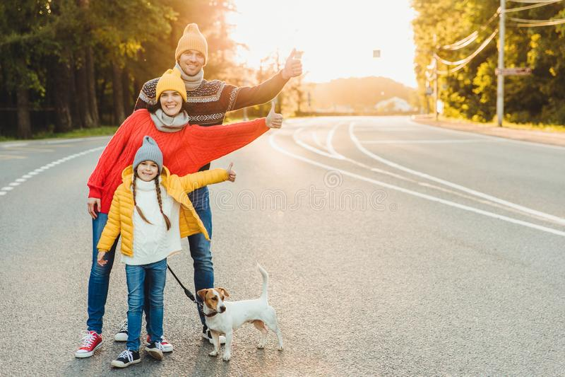 Le portrait extérieur de la jolie femme, son mari et la fille montrent le signe correct, marchent avec le chien sur la route, app photographie stock libre de droits