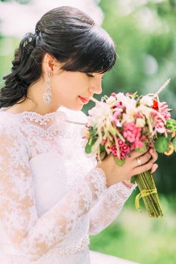 Le portrait extérieur latéral en gros plan de la jolie jeune mariée sentant le bouquet coloré de mariage photos libres de droits