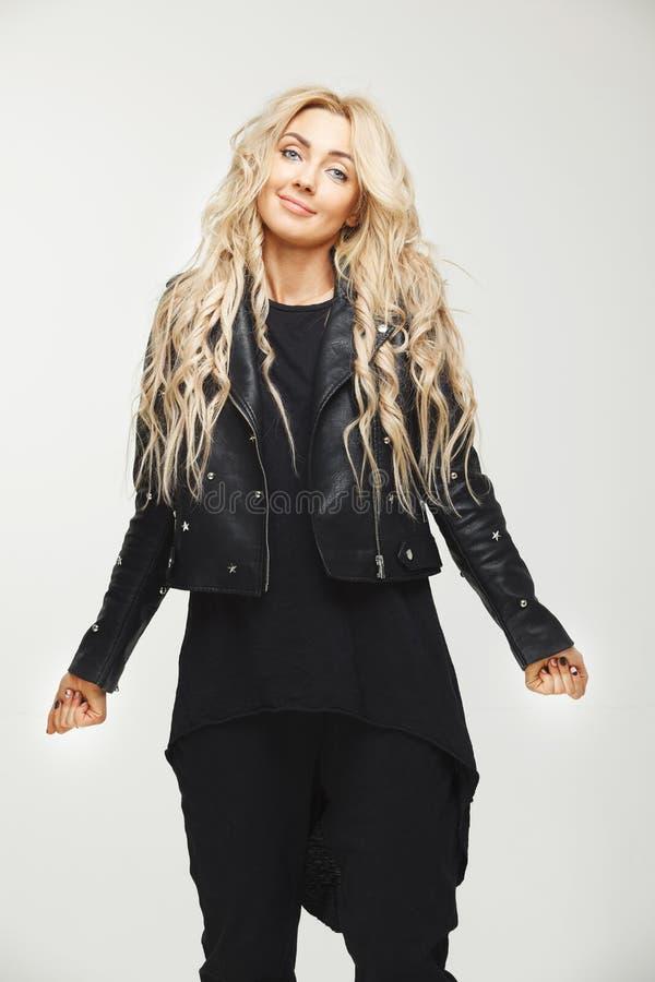 Le portrait femelle vertical de la blonde dans des vêtements noirs, levage ennuyeux épaule du désespoir ou de l'ignorance confusi photos stock