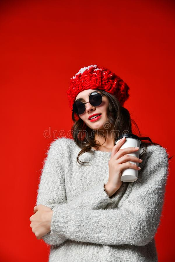 Le portrait haut étroit d'une jeune fille de sourire dans se tenir de chapeau emportent la tasse de café photos libres de droits