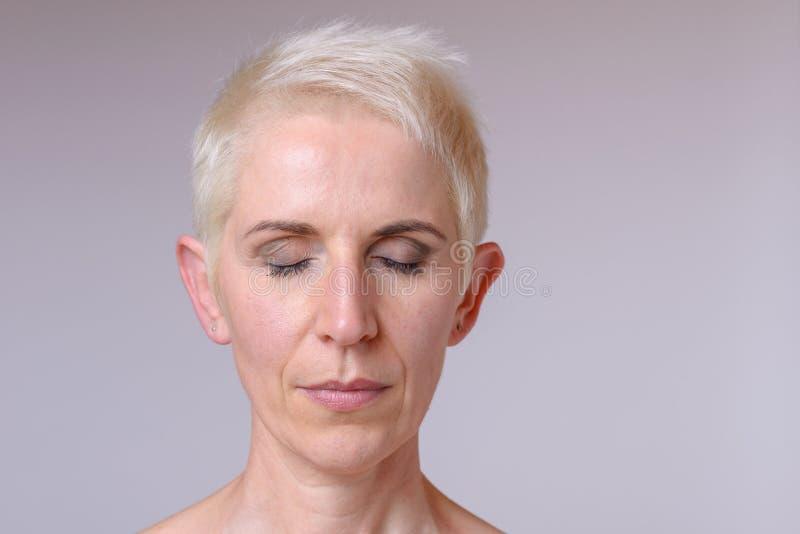 Le portrait haut étroit de bandeau d'un milieu a vieilli la femme photographie stock