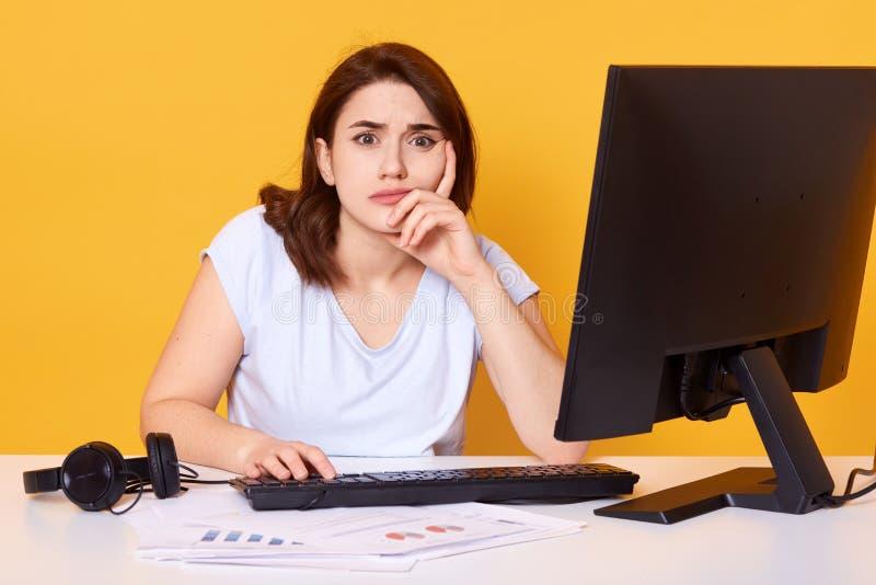 Le portrait haut étroit de l'étudiant universitaire féminin assez jeune utilisant l'ordinateur de bureau à une bibliothèque  photo libre de droits