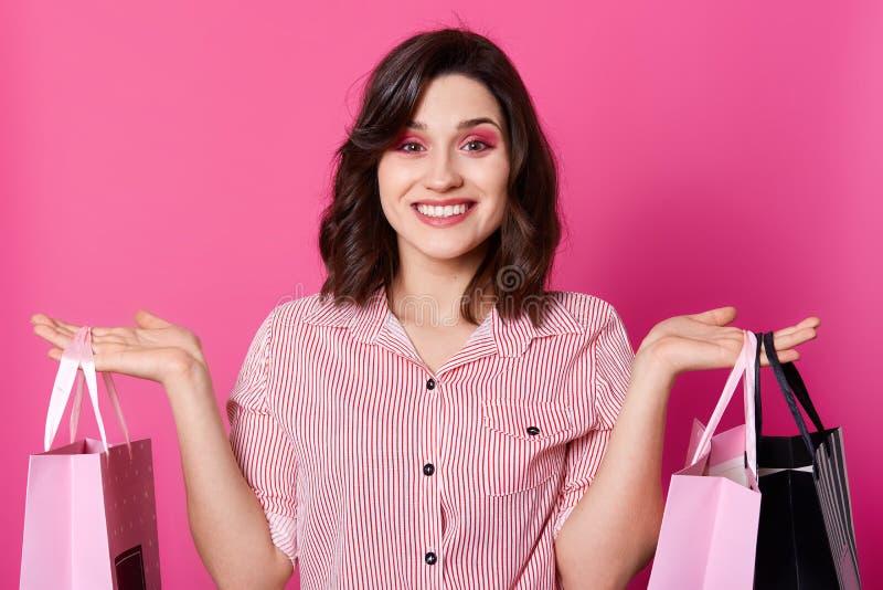 Le portrait haut étroit de la belle femme de sourire heureuse de brune avec les cheveux onduleux, chemise rayée habillée, tient l image stock