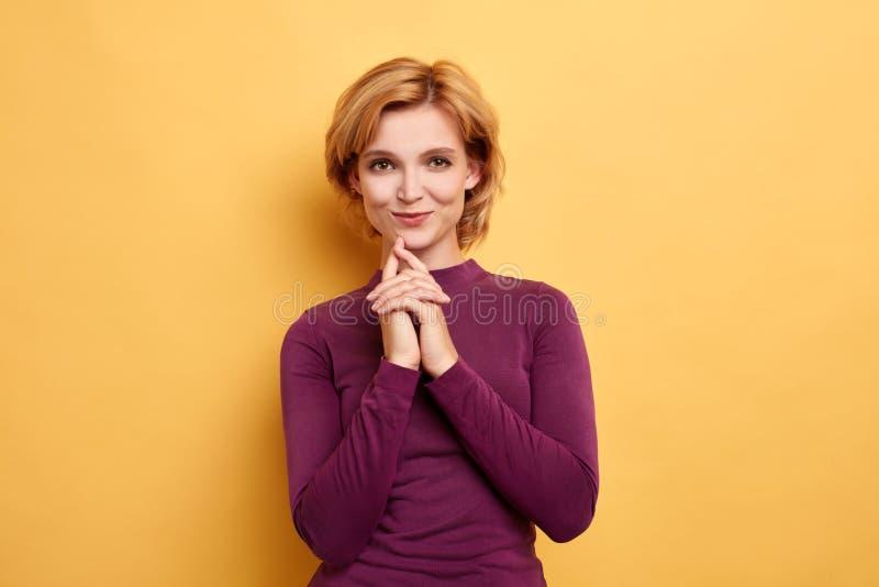 Le portrait haut étroit de la femme blonde attirante garde des mains ensemble sous le coffre image stock