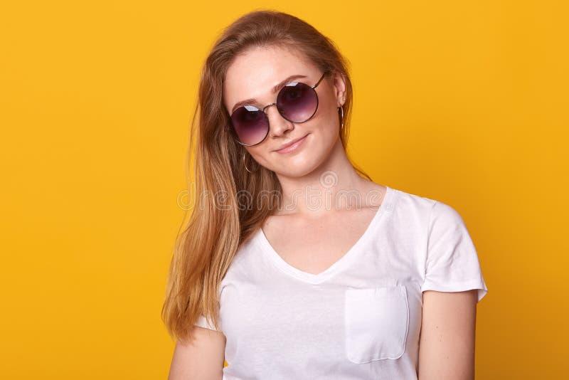 Le portrait haut étroit de la femme mignonne avec le sourire avec du charme et avec la longue coiffure blonde, utilise le T-shirt image stock
