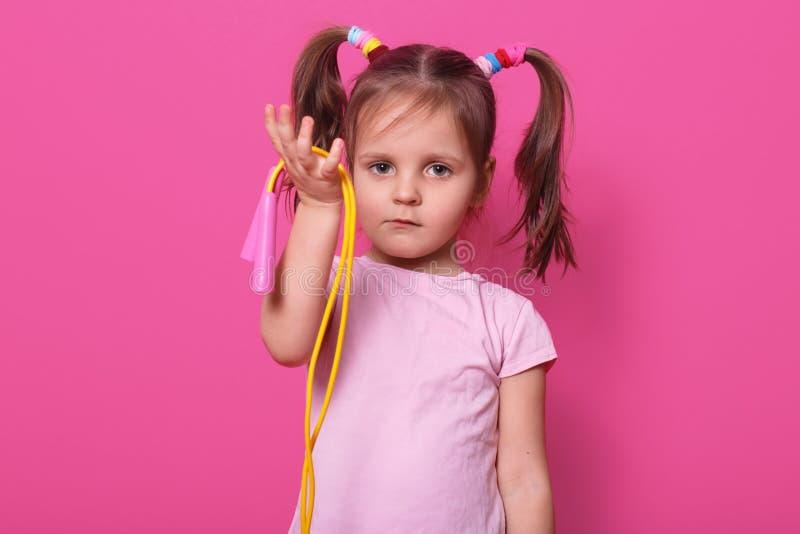 Le portrait haut étroit de la fille mignonne et triste tient à disposition la corde à sauter Peu enfant veut jouer avec quelqu'un photographie stock libre de droits