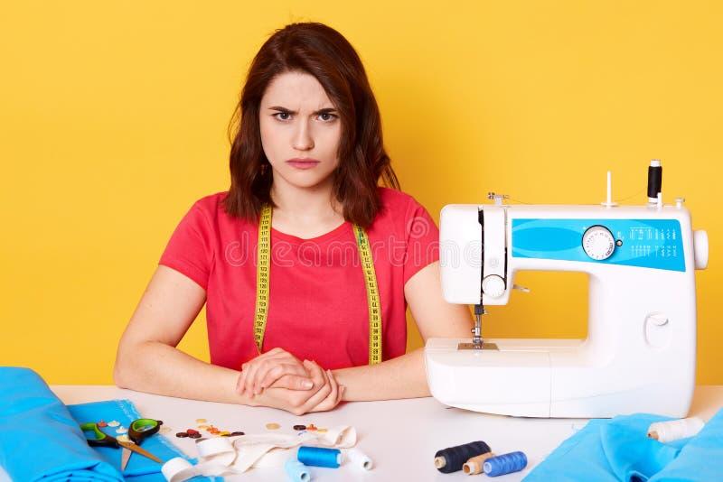 Le portrait haut étroit de la séance d'ouvrière couturière de jeune femme et coud sur la machine à coudre, regarde fâché la camér photographie stock libre de droits