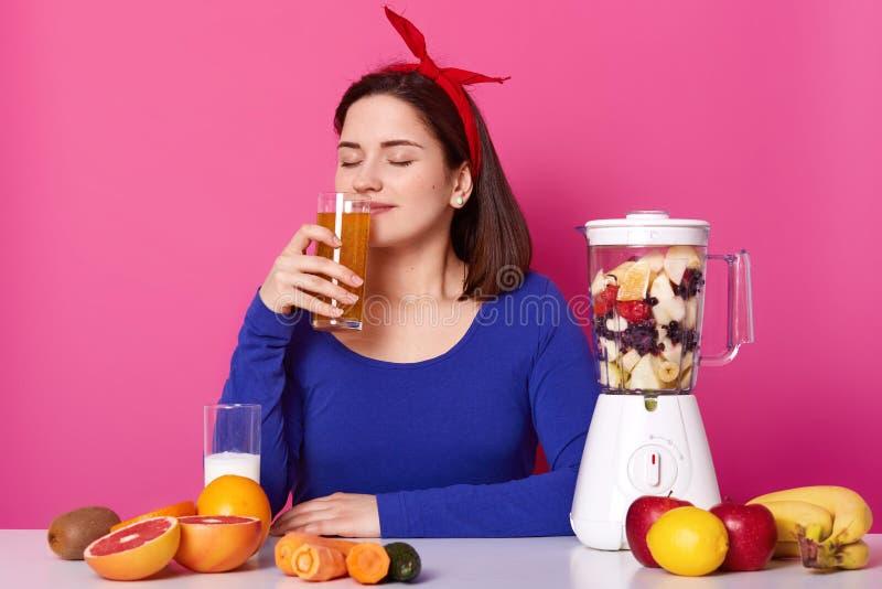 Le portrait haut étroit du smoothie sentant avec du charme agréable de fruit de jeune dame avec les yeux fermés, apprécie l'o photos stock
