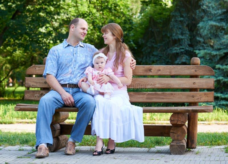 Le portrait heureux de famille avec le bébé sur extérieur, se reposent sur le banc en bois en parc de ville, saison d'été, enfant photo libre de droits