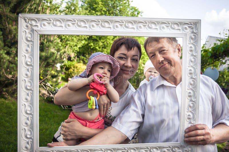 Le portrait heureux de famille du grand-père gai avec sa fille et l'petit-enfant pendant l'extérieur font la fête images stock