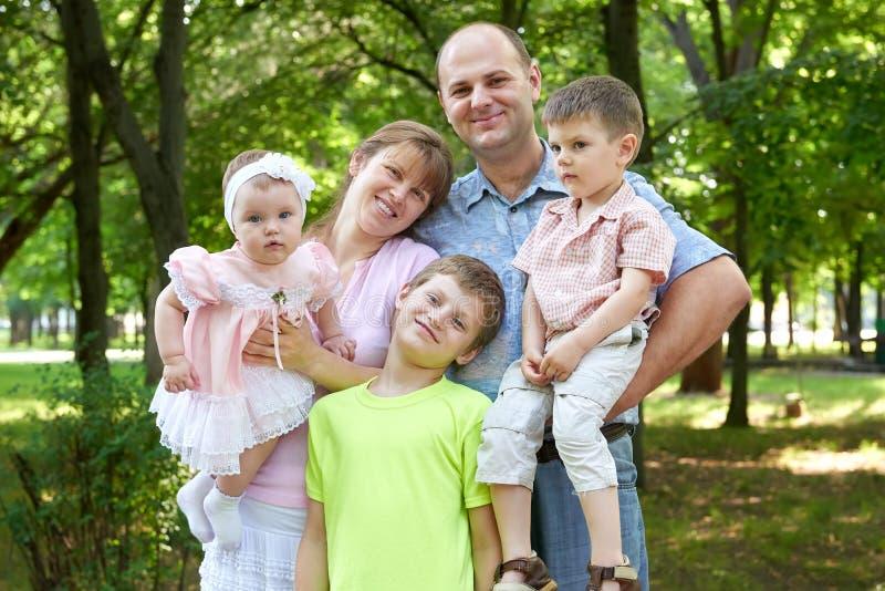 Le portrait heureux de famille sur extérieur, groupe de cinq personnes posant dans la ville se garent, saison d'été, enfant et pa photo libre de droits