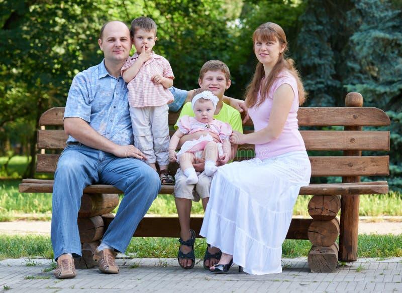 Le portrait heureux de famille sur extérieur, groupe de cinq personnes se reposent sur le banc en bois en parc de ville, saison d image stock