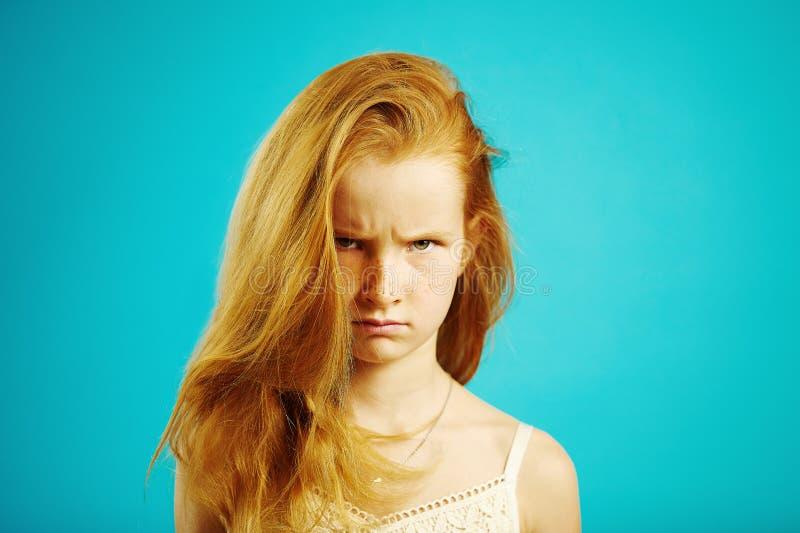 Le portrait horizontal de la fille d'une chevelure rouge fâchée avec l'expression sombre démontre la colère et le mécontentement, image stock