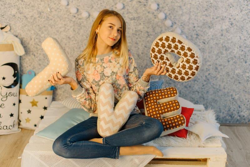 Le portrait horizontal de la jeune adolescente tenant les coussins avec des lettres d'amour photo stock